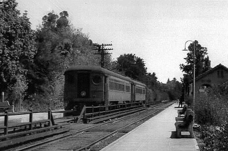"Northwestern Pacific electric train at Ross Station on its southbound run to the ferry terminal at Sausalito. This is 1938 and the system had less than three years more to operate. The steel electric cars got their power from a ""third rail"" beside the tracks (under the board covers on both sides of the fence)."