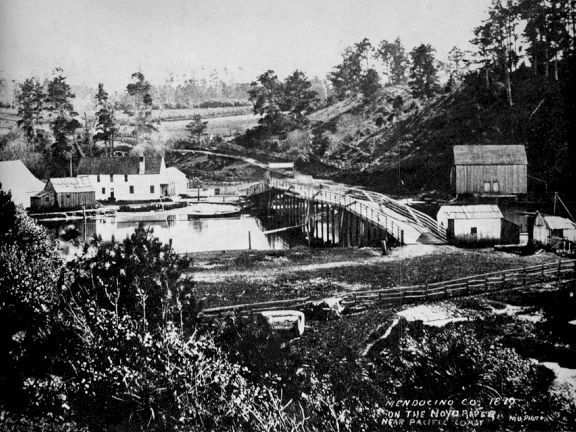 Looking south across the first bridge over the Noyo circa 1870. John Byrne and John Warrington were given a franchise to build a toll drawbridge to replace the ferry that had been there. The road that became South Harbour Drive is a meandering dirt road.