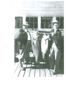 1940 Two fishermen holding catch