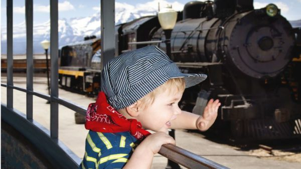 Little boy waving at train