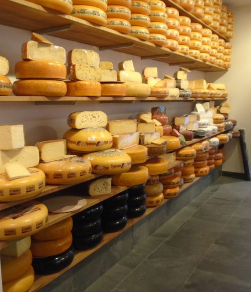 A wall of some thirty different types of cheeses