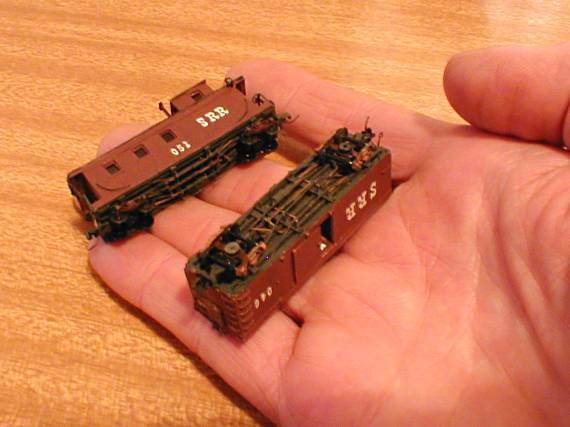 Two Nn3 freight cars on the fingers of a hand